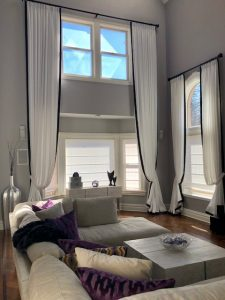 Pleated Draperies in High Windows in Living Room